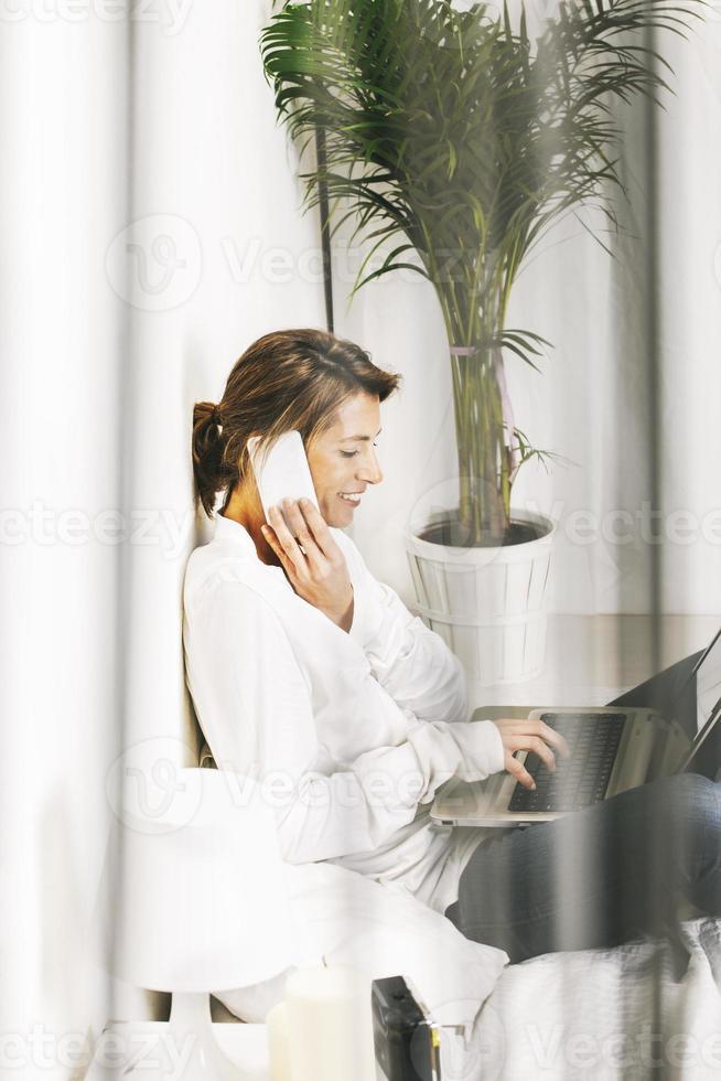 schöne reife Geschäftsfrau, die mit Laptop im Bett arbeitet. foto
