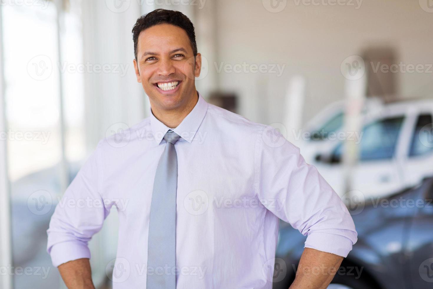 Verkäufer mittleren Alters, der beim Autohaus steht foto