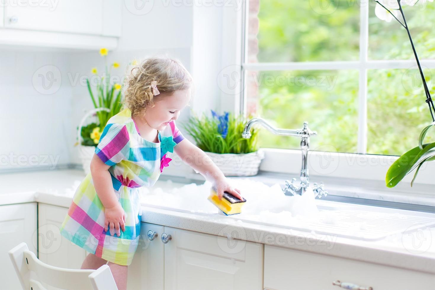 süßes lockiges Kleinkindmädchen, das Geschirr spült, mit Schwamm putzt foto