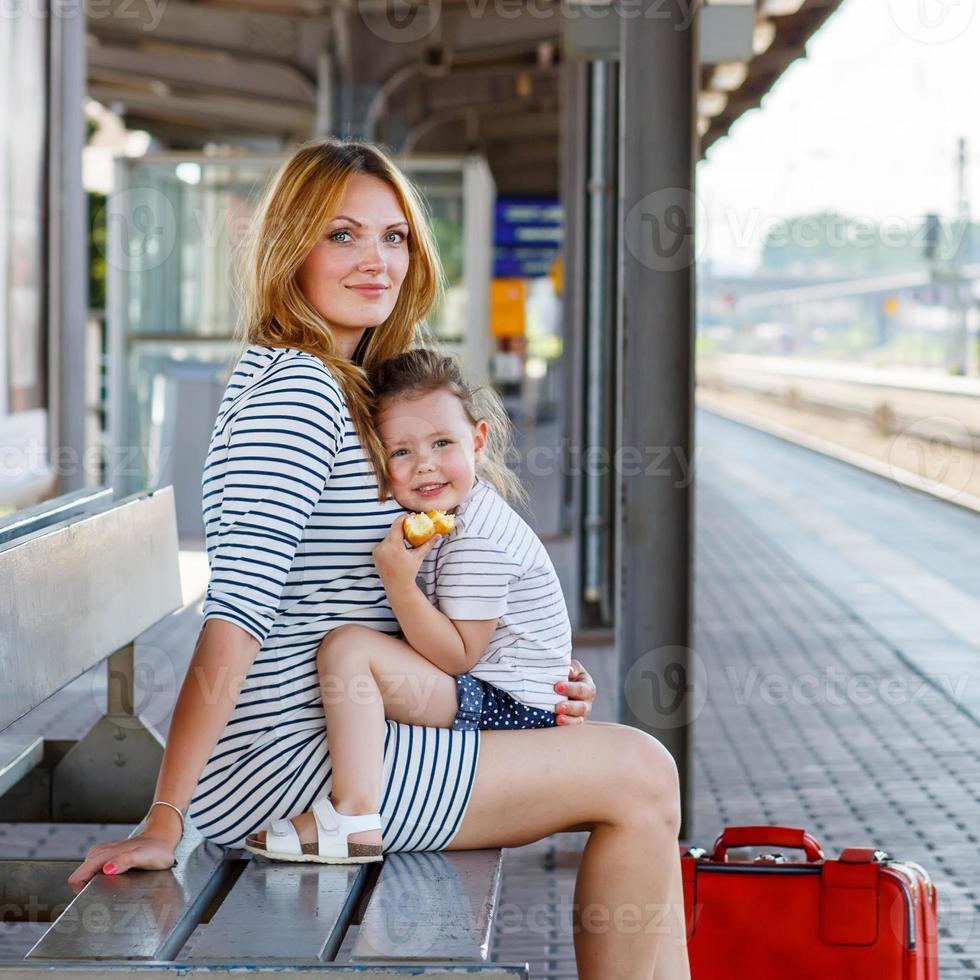 süßes kleines Mädchen und Mutter auf einem Bahnhof. foto