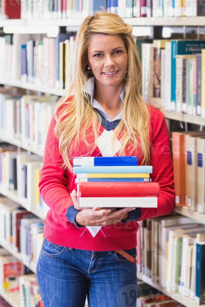 reifer Student in der Bibliothek mit Büchern foto
