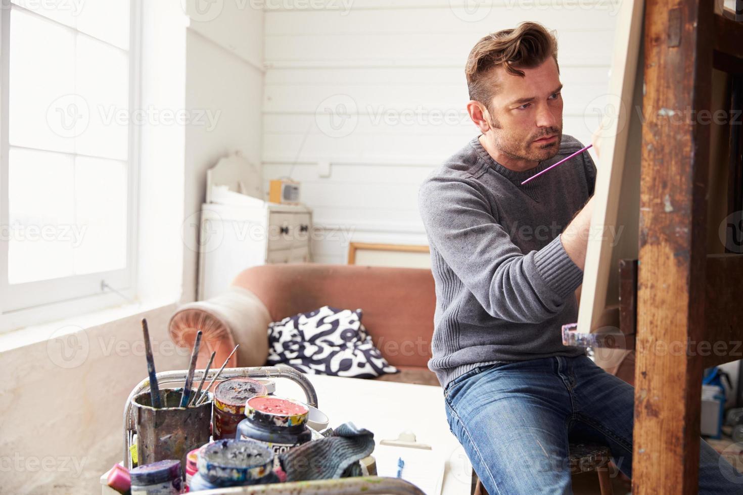 männlicher Künstler, der an der Malerei im Studio arbeitet foto