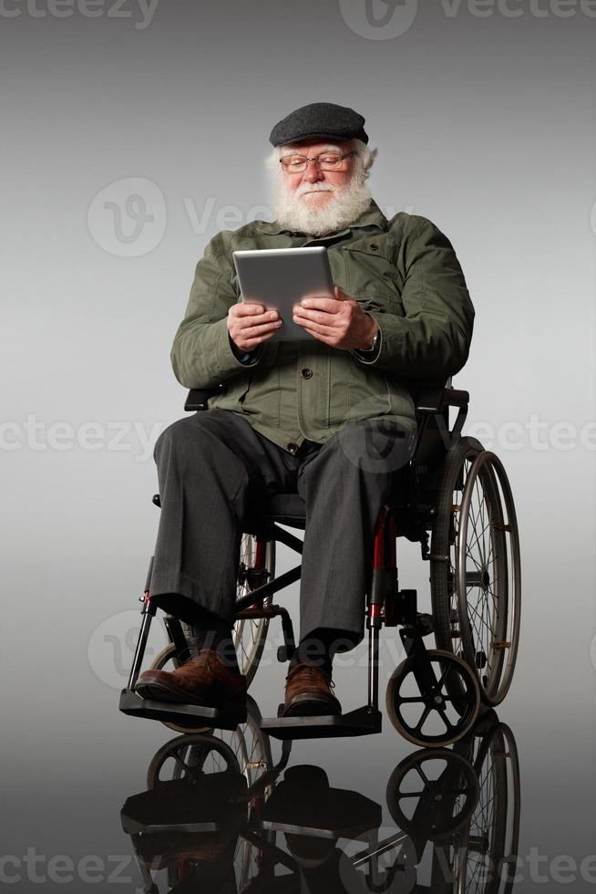 älterer Mann auf Rollstuhl mit digitaler Tablette foto