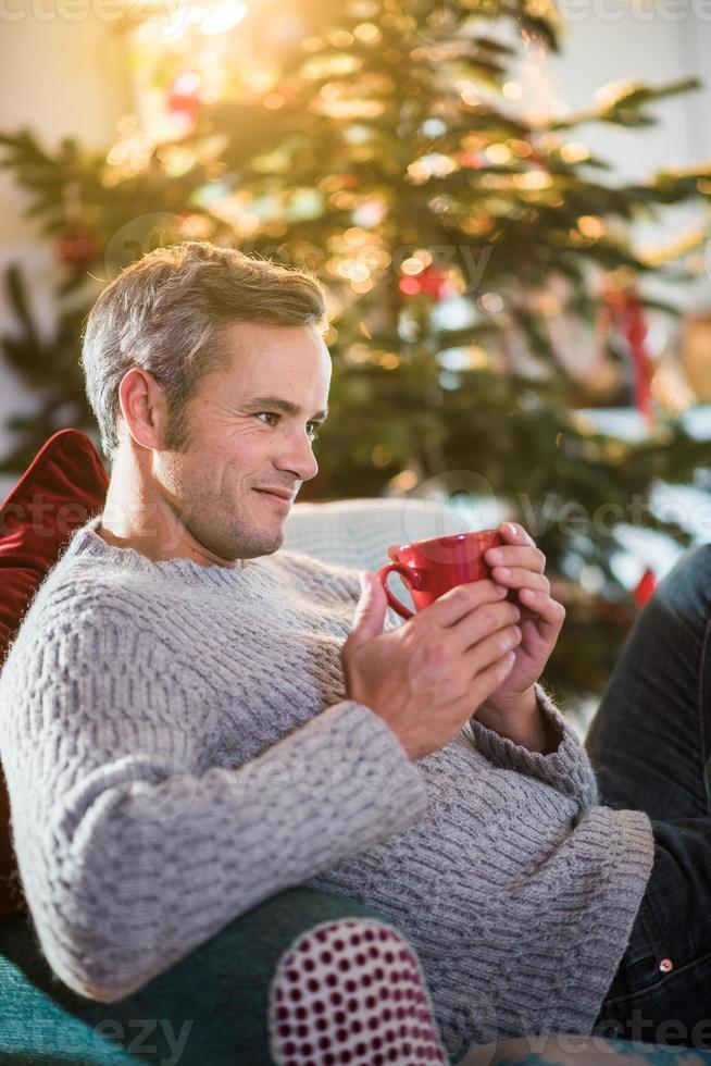 Weihnachtsmorgen, Mann, der eine Tasse nahe Weihnachtsbaum hält foto