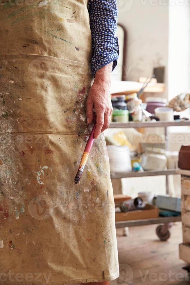 Nahaufnahme der Künstlerin, die Pinsel im Studio hält foto