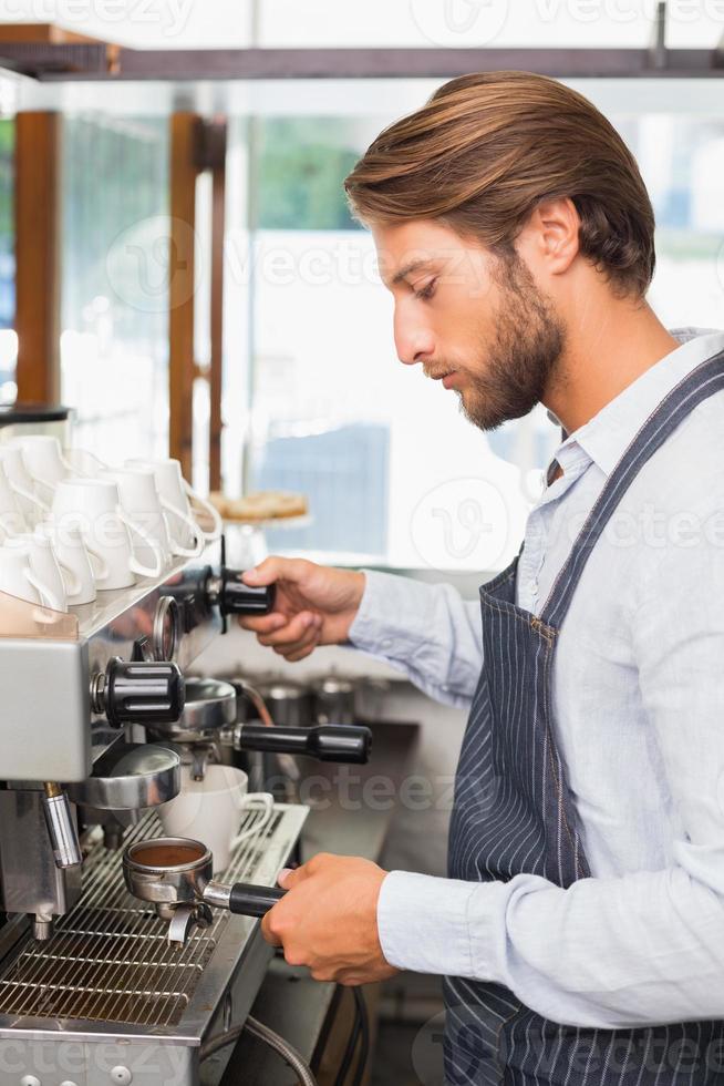 hübscher Barista, der eine Tasse Kaffee macht foto