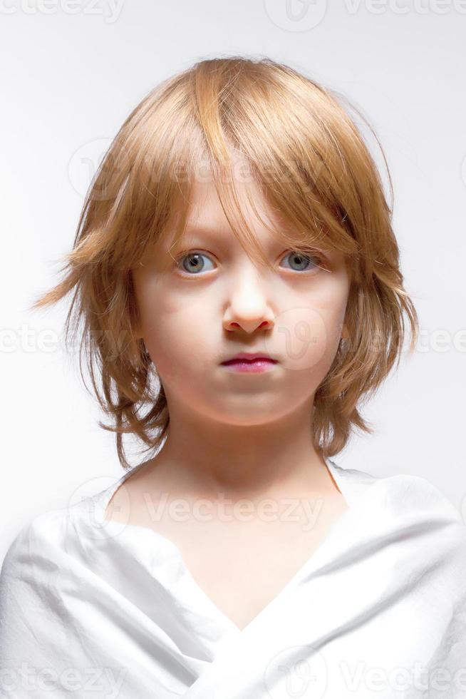 Junge mit blonden Haaren suchen - isoliert auf grau foto