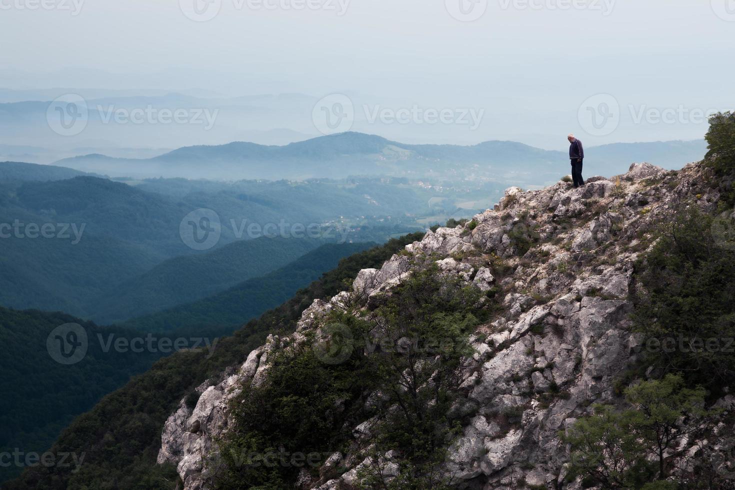 älterer Mann, der am Rand der Klippe steht foto