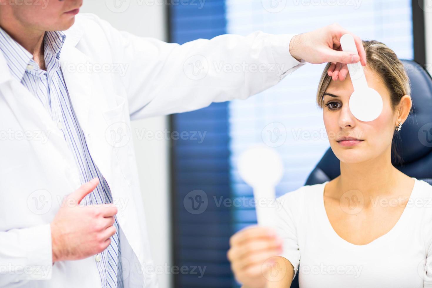 hübsche junge Frau, deren Augen durch Optometrie untersucht werden foto