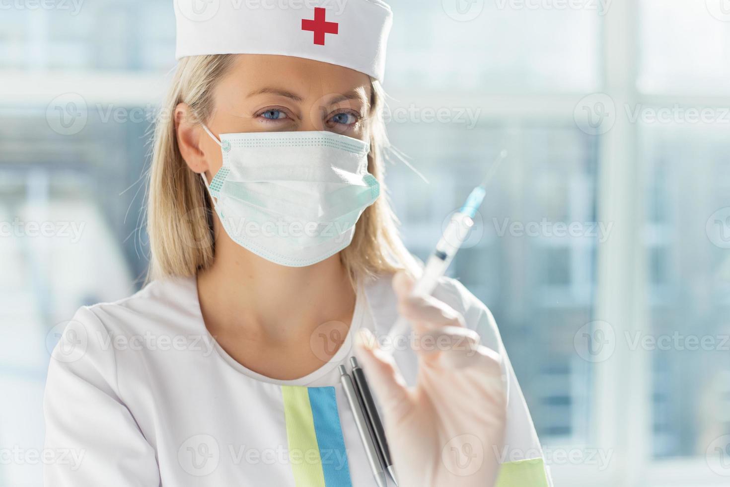 Krankenschwester hält Spritze foto