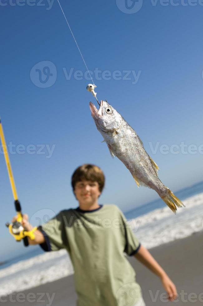 Junge zeigt Fisch foto