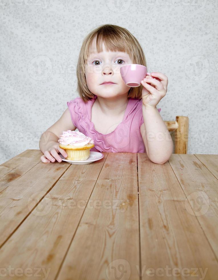 Haltung Tee-Party - Mädchen mit rosa Tasse und Cupcake foto