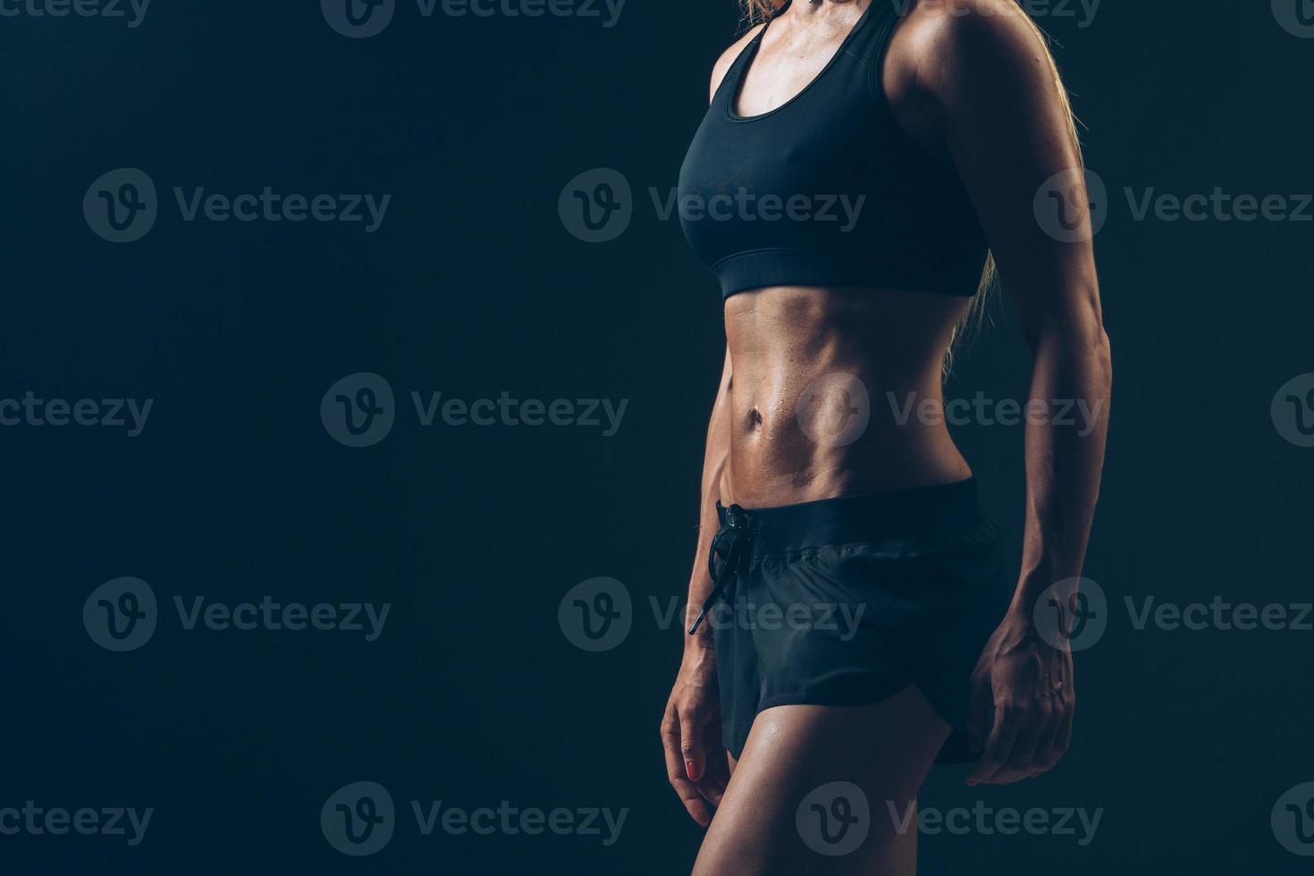 Sportfrauenporträt, das schwarze Sportbekleidung über Dunkelheit trägt foto