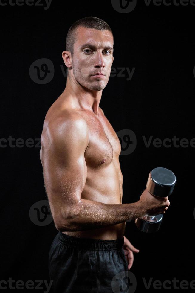 Porträt des selbstbewussten hemdlosen Athleten, der mit Hantel arbeitet foto