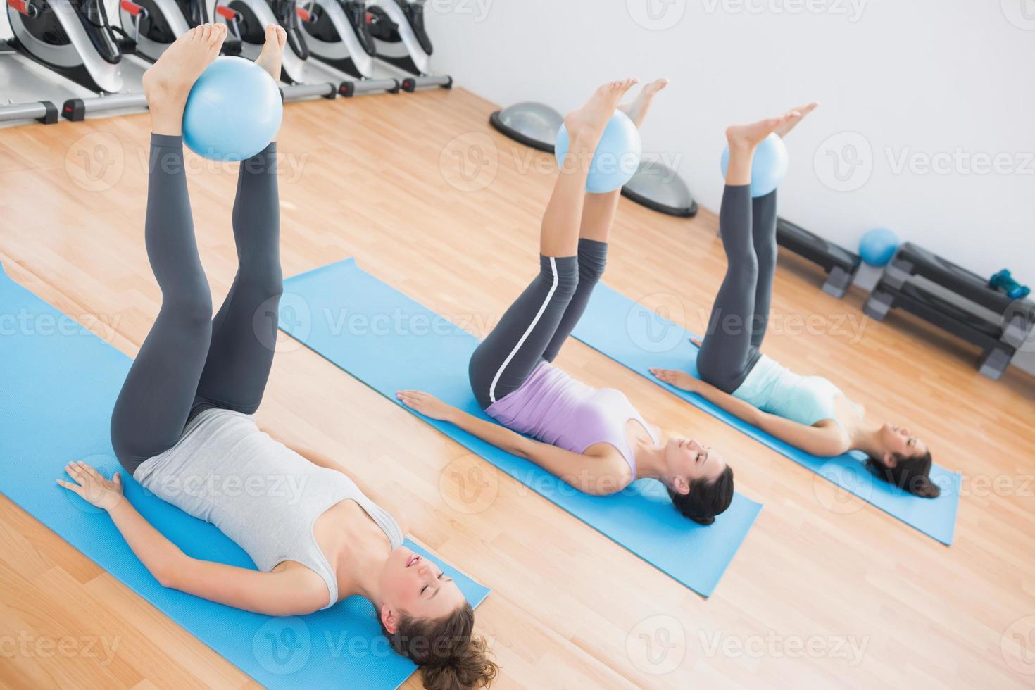 sportliche Frauen, die Bälle zwischen den Knöcheln im Fitnessstudio halten foto