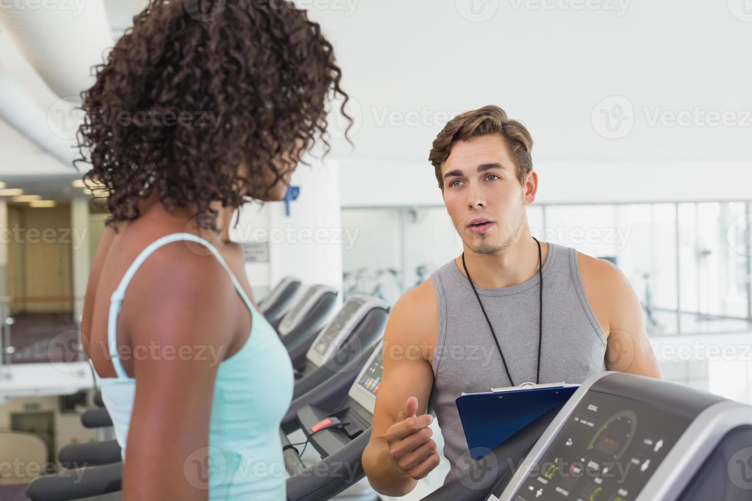 Fit Frau auf dem Laufband im Gespräch mit Personal Trainer foto