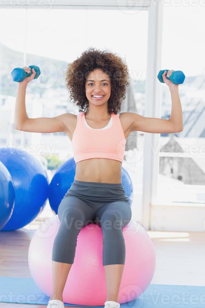 Frau, die mit Hanteln auf Fitnessball im Fitnessstudio trainiert foto