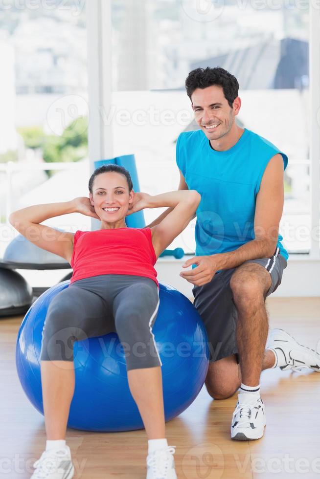 männlicher Trainer, der Frau mit ihren Übungen im Fitnessstudio hilft foto