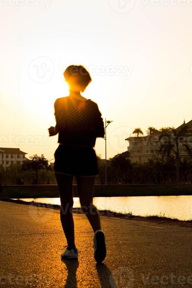 Läuferathletenfüße, die auf Straße laufen. Frau Fitness Silhouette su foto