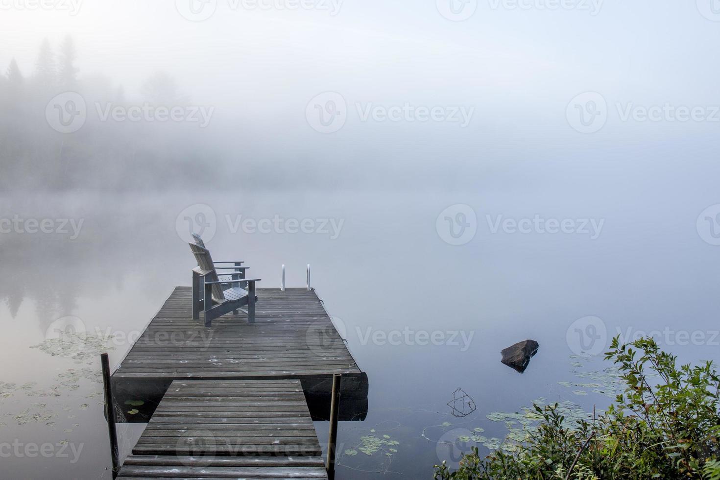 Stühle auf einem Dock mit Blick auf einen nebligen See foto
