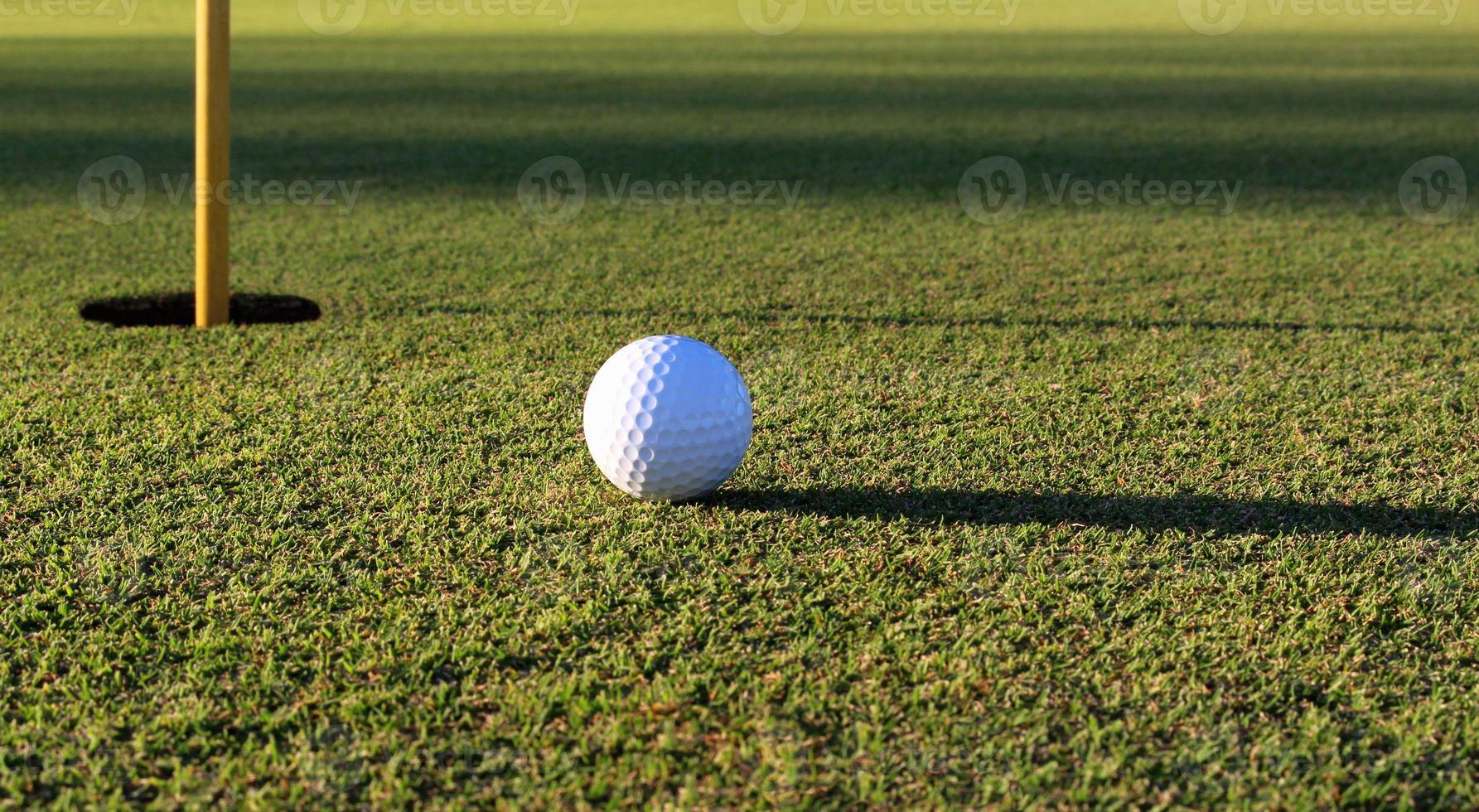 Golfball in der Nähe der Tasse foto