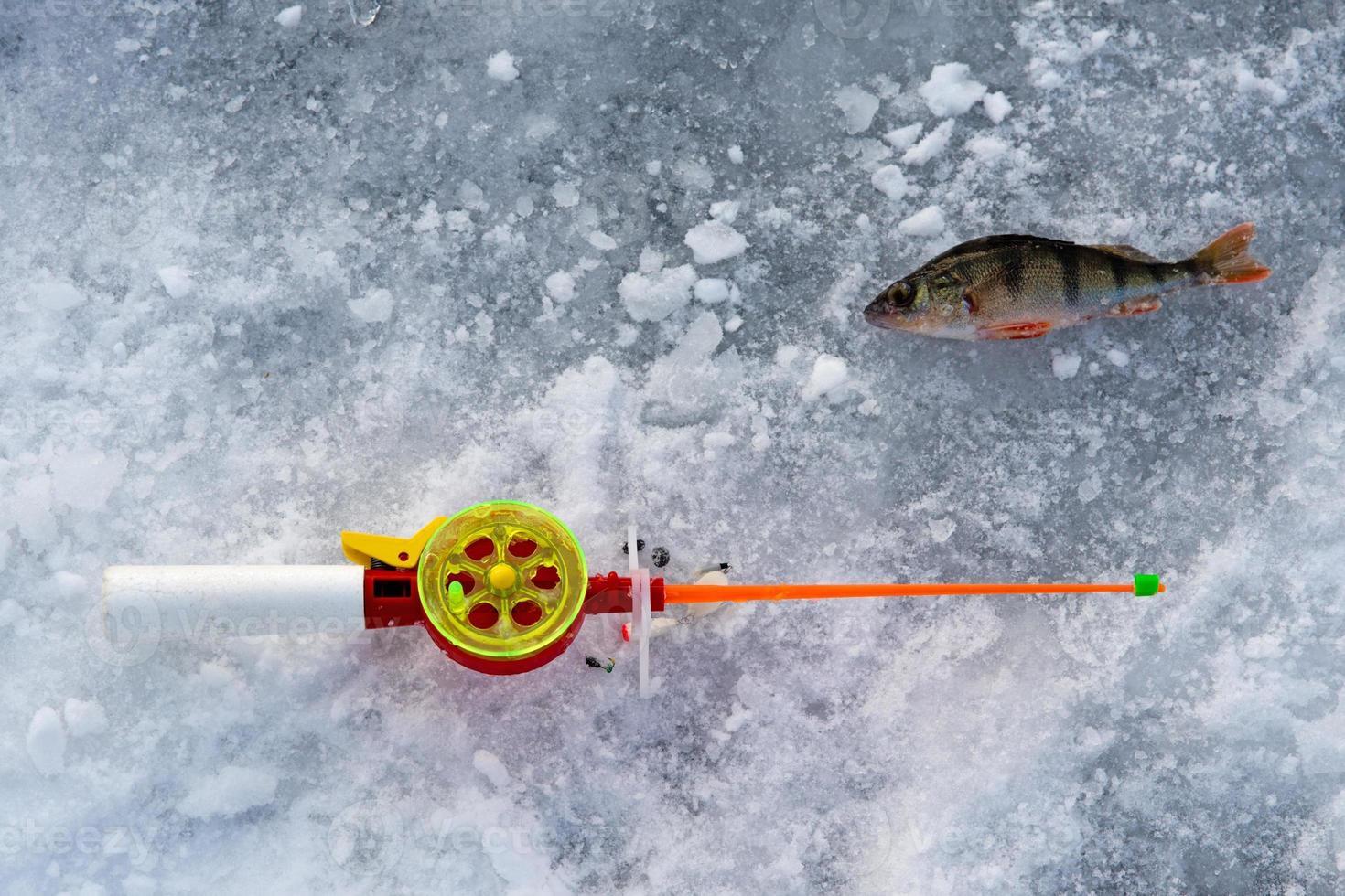 Die Rute zum Winterfischen liegt in der Nähe eines Lochs foto