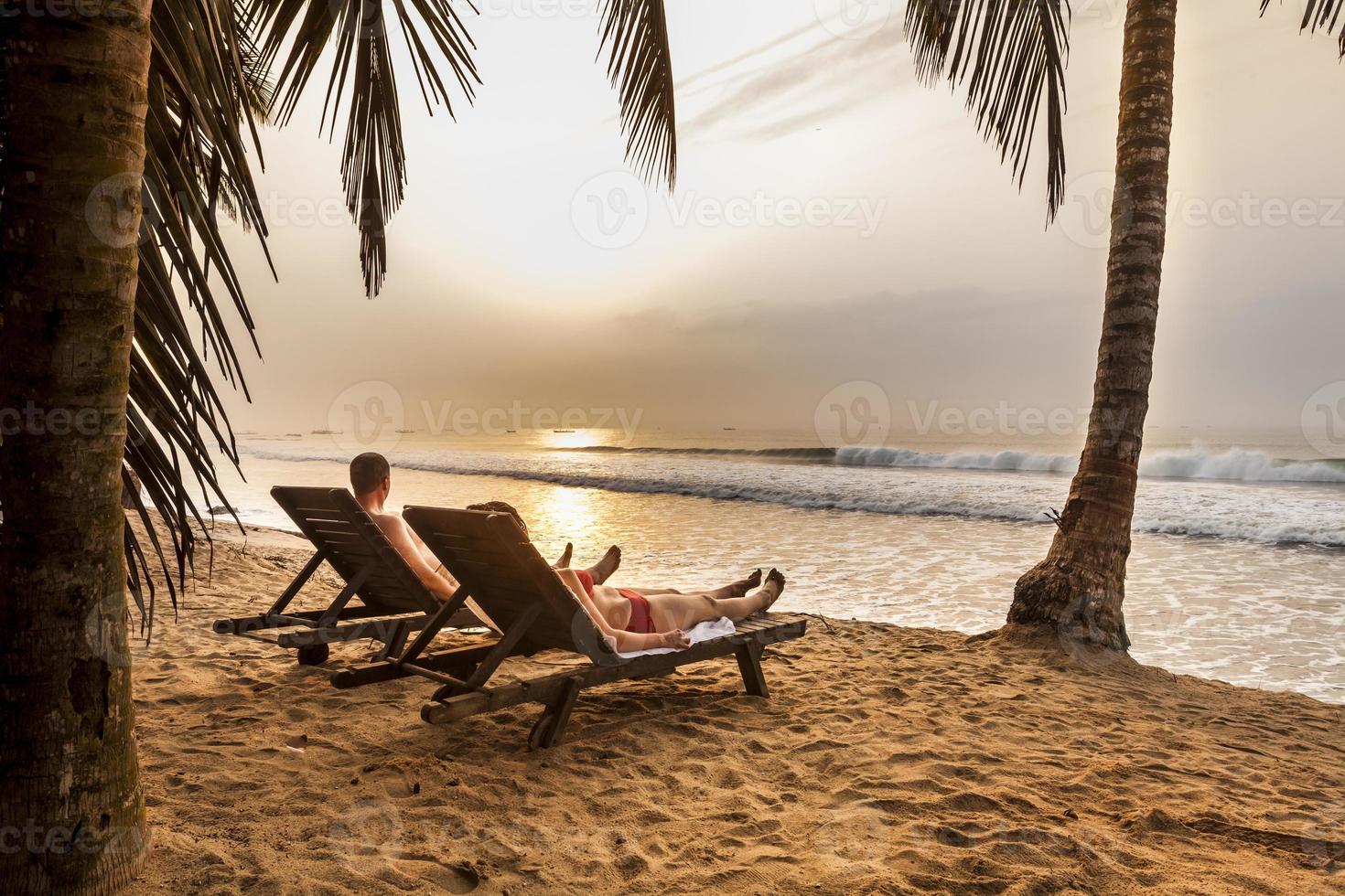Paar auf den Sonnenliegen am tropischen Strand foto