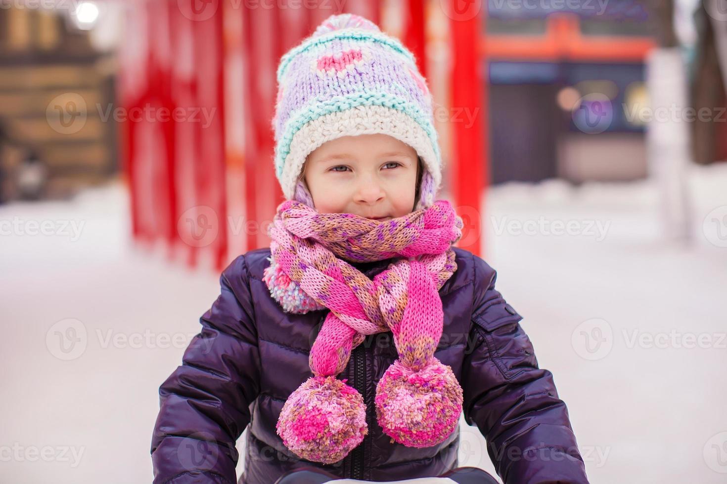 entzückendes kleines glückliches Mädchen, das auf der Eisbahn Schlittschuh läuft foto