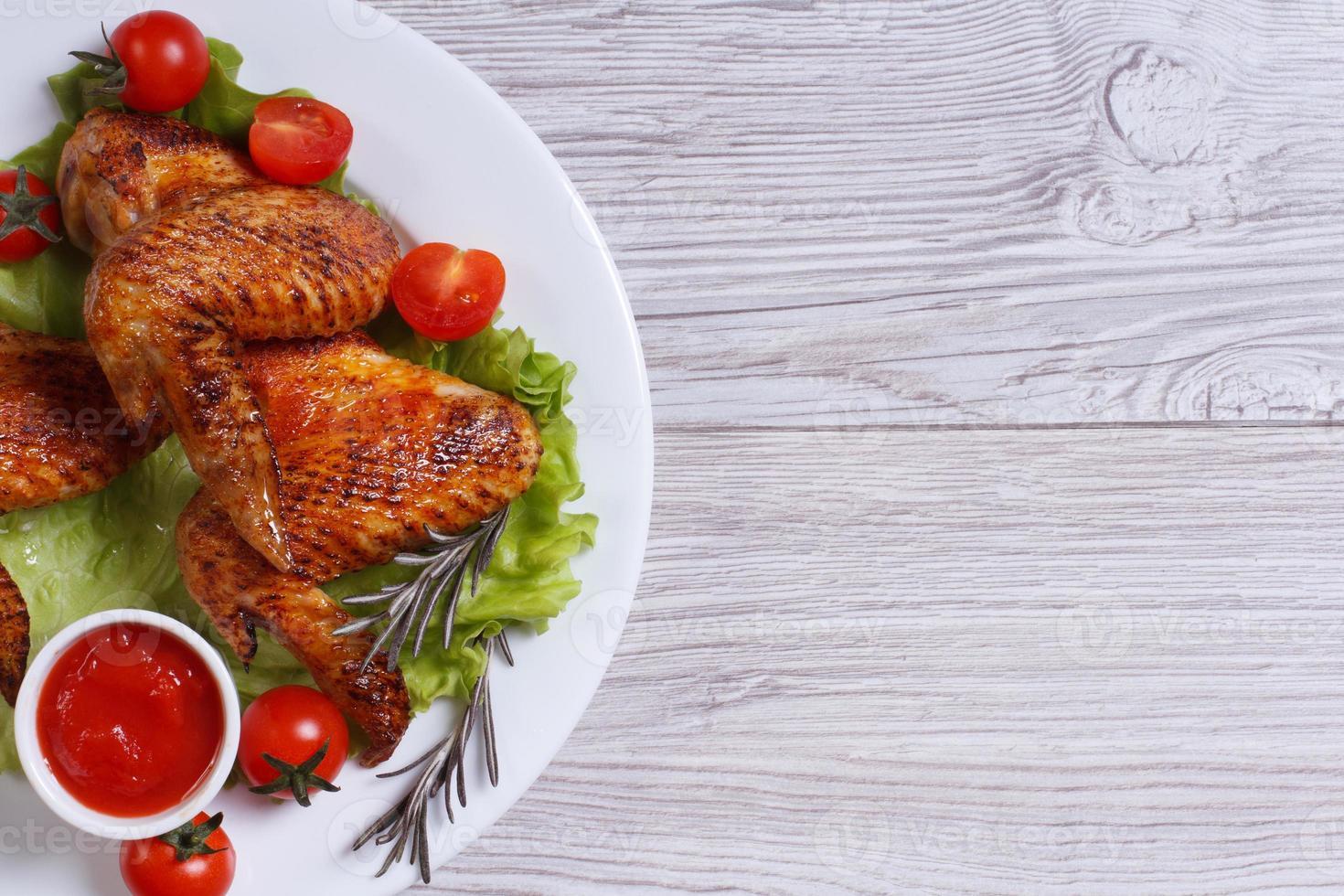 gebratene Hühnerflügel mit Sauce und Gemüse Draufsicht foto