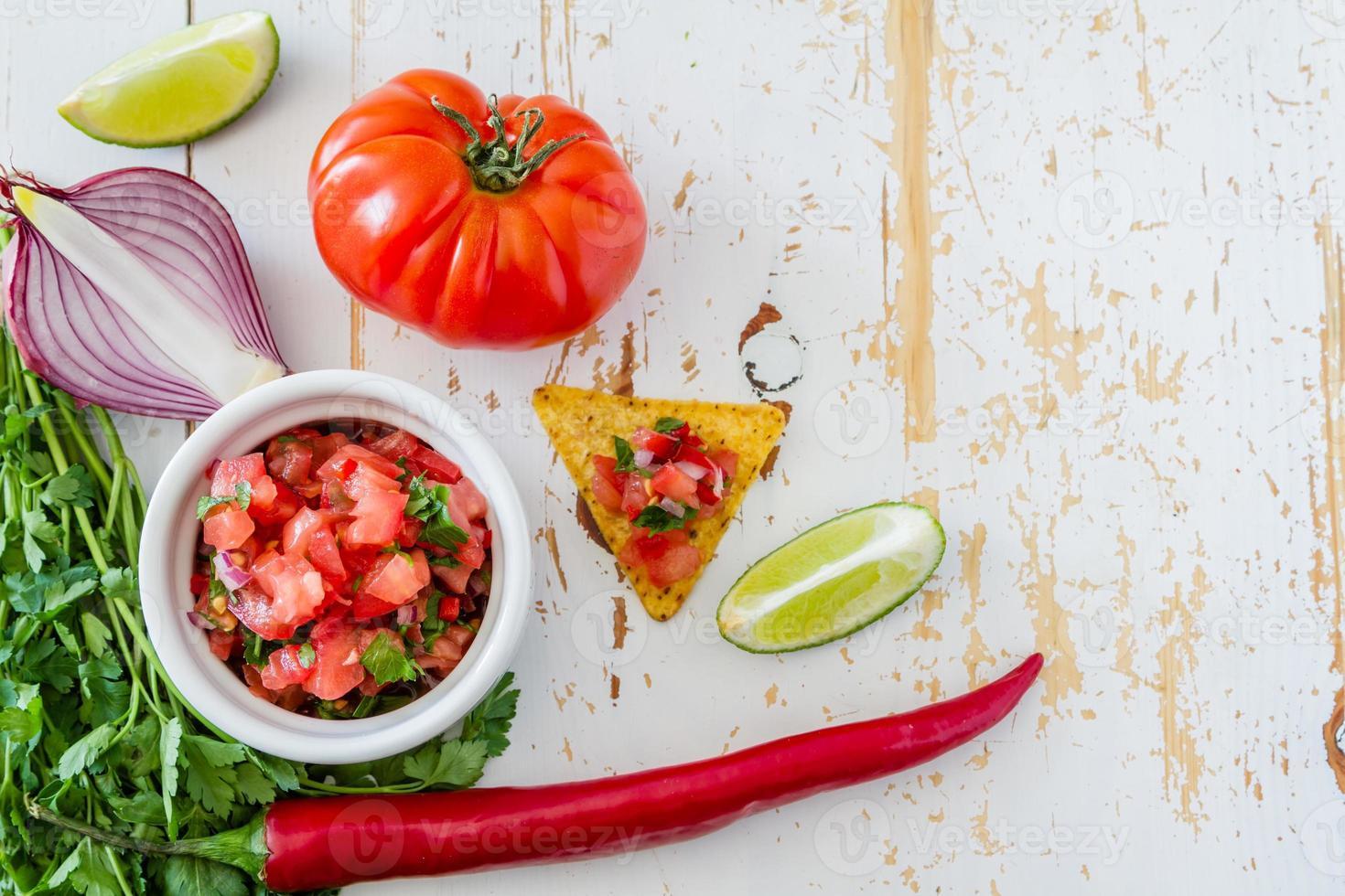 Salsasauce und Zutaten - Tomaten, Chili, Zwiebel, Limette, Petersilie foto
