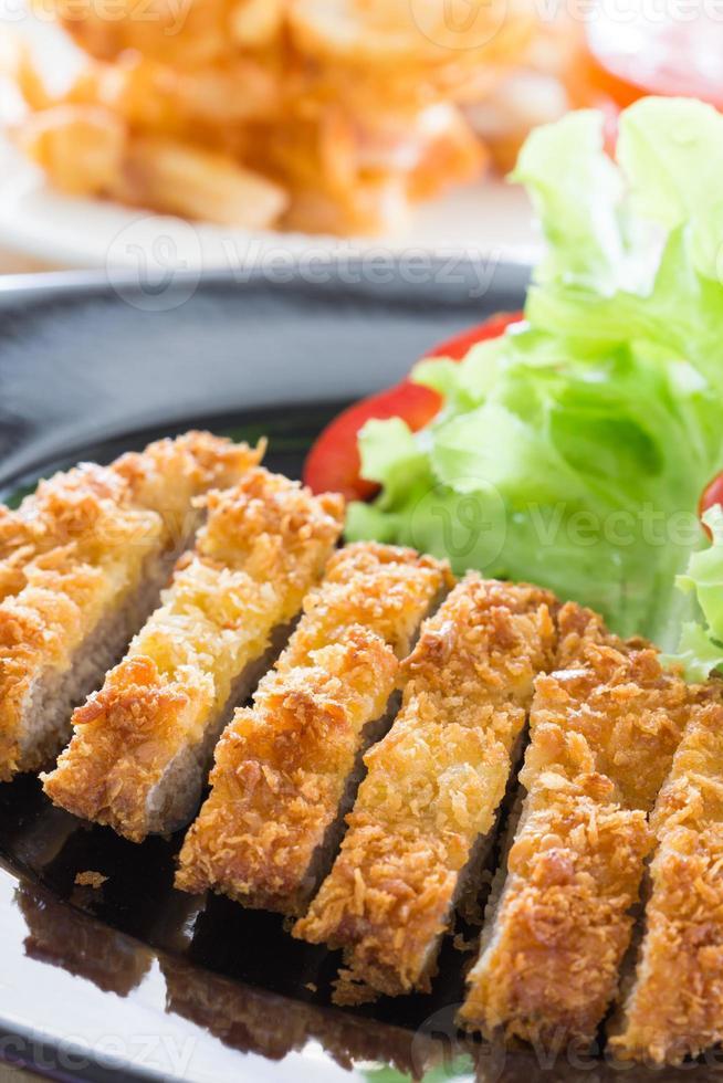 frittierter panierter Schweinefleischreis mit Salat foto