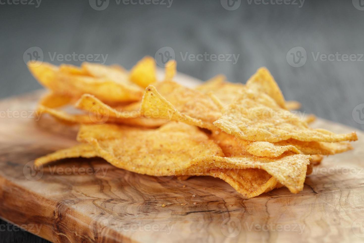 Haufen Tortillachips auf Olivenbrett auf Holztisch foto