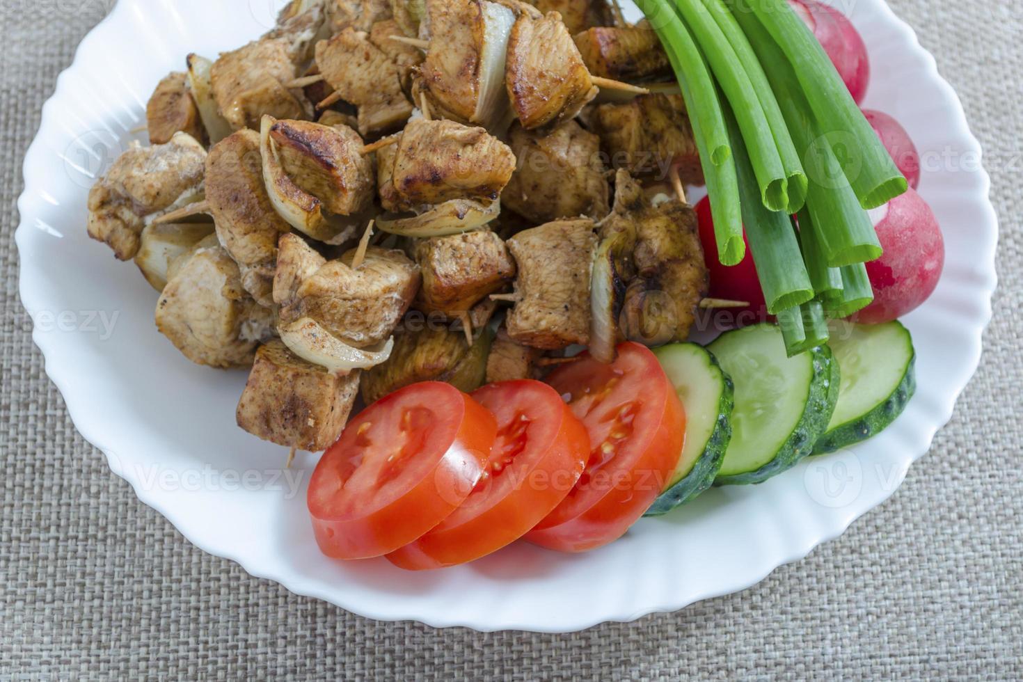 Mini-Spieße mit Hühnchen und eine Beilage mit Gemüse foto