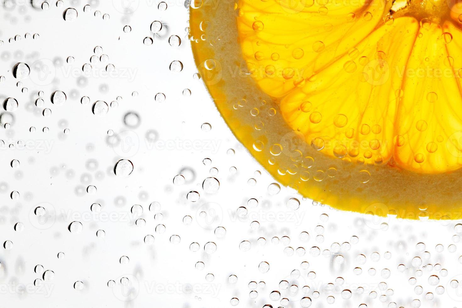 eine Scheibe Zitrusorange in einem Glas Wasser foto