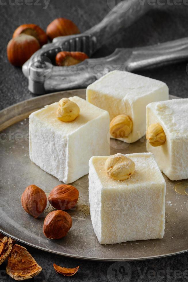 türkisches Entzücken. östliches Dessert mit Haselnuss auf Metallplatte. selektiv foto