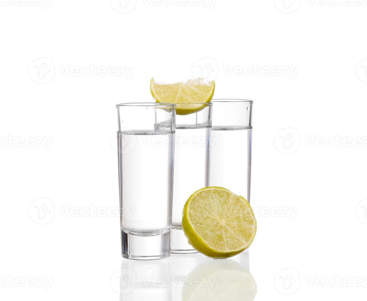 drei Tequila-Schüsse mit Kalk lokalisiert auf weißem Hintergrund foto