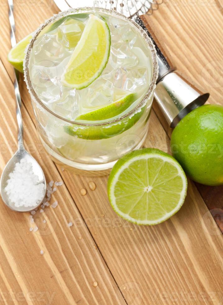 klassischer Margarita-Cocktail mit salzigem Rand auf Holztisch foto
