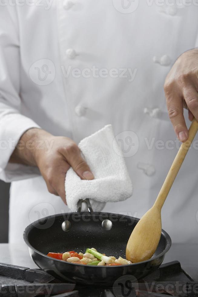 Mittelteil des Küchenchefs, der Essen kocht foto