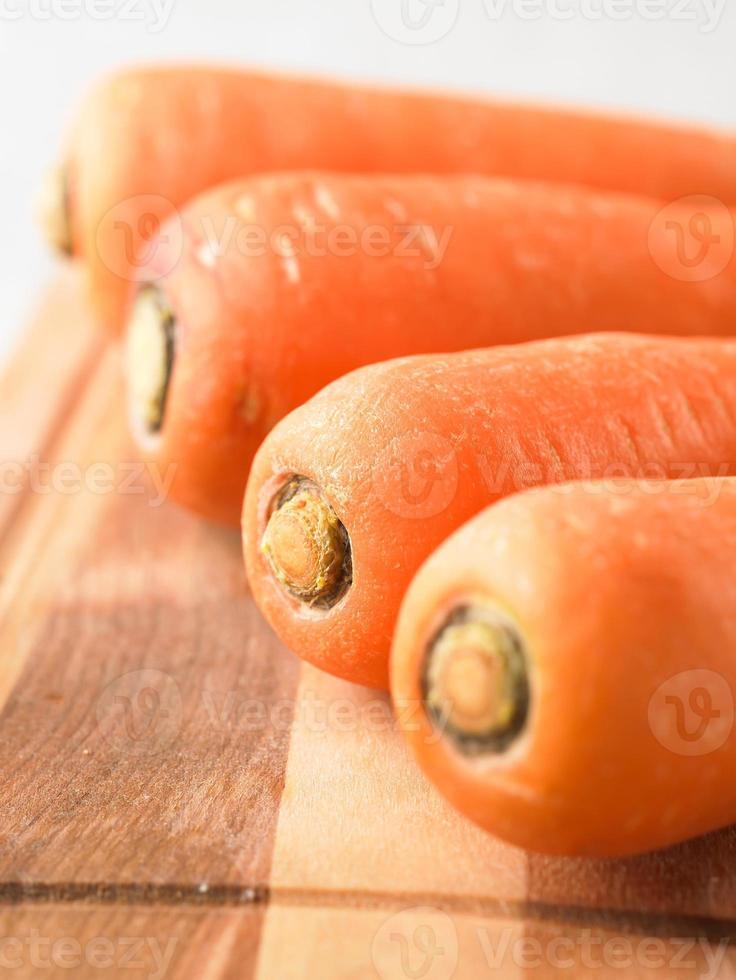 schließen Sie frische und süße Karotte auf Holzteller foto