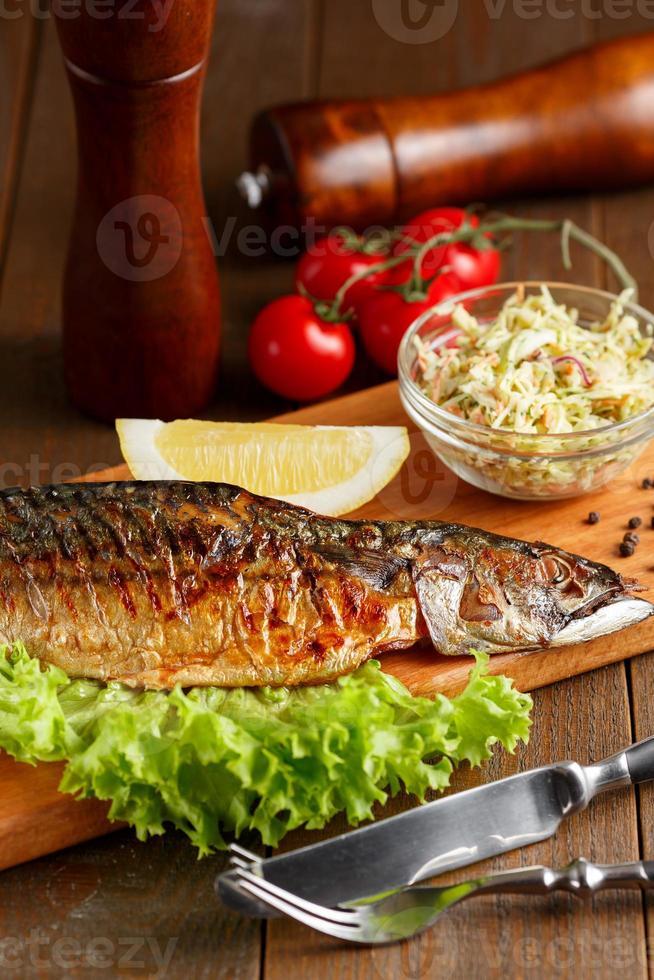Gebratene Makrele mit Zitronenscheibe und Salat foto
