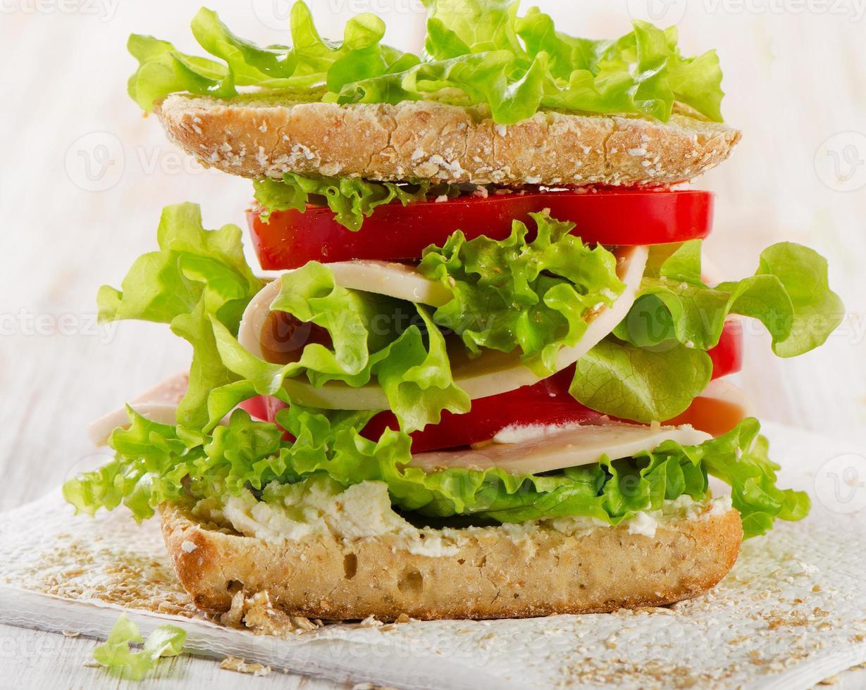 Sandwich mit Truthahn und frischem Gemüse auf einem hölzernen Hintergrund foto