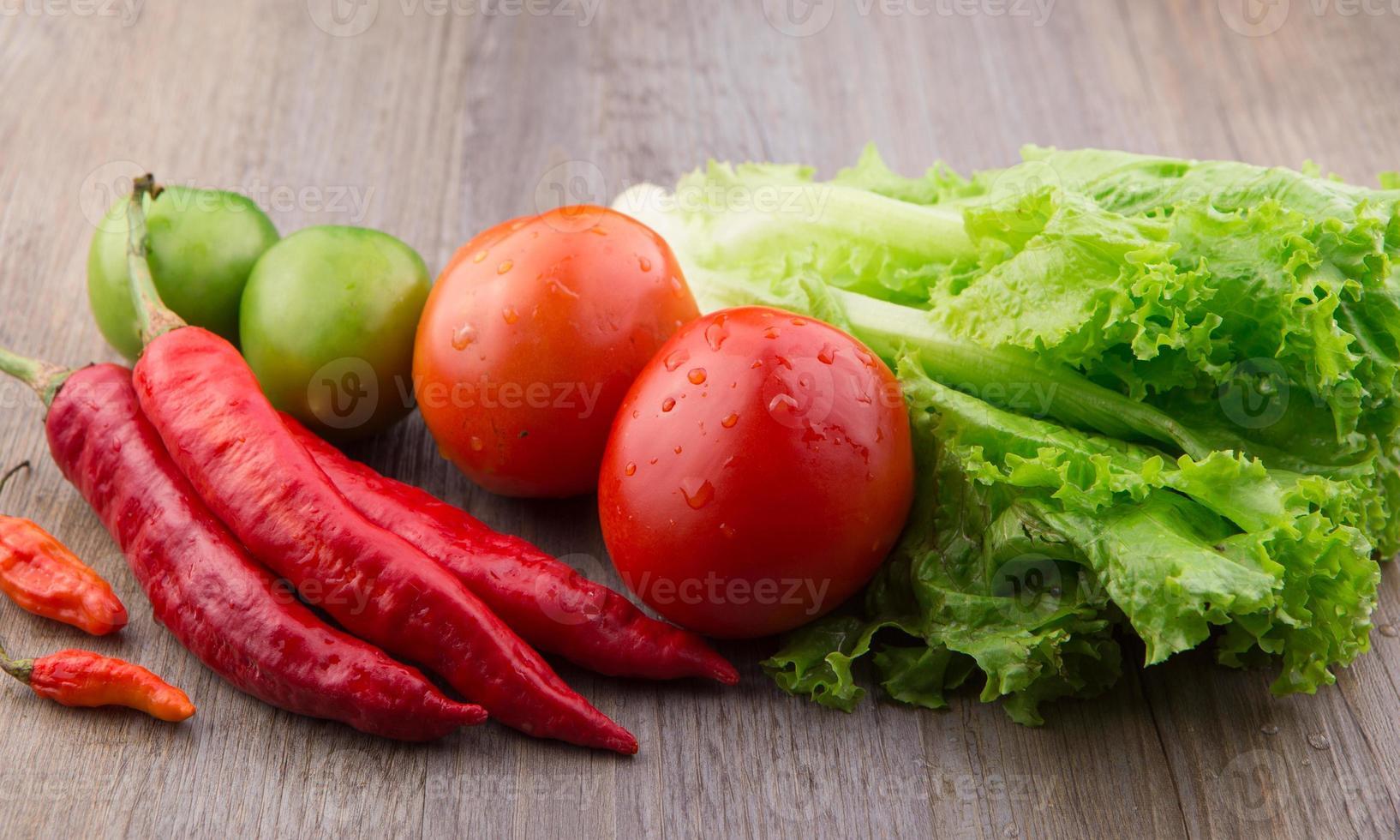 rote Chilis, Vogelaugen-Chilis, Salat, rote und grüne Tomaten foto