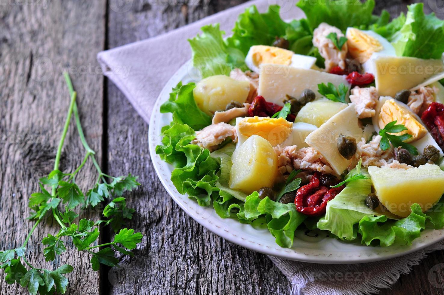 Salat aus Salat, Eisbergsalat, mit Thunfischkonserven, getrockneten Tomaten foto