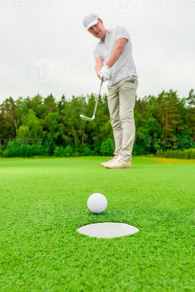 vertikaler Bildmann, der Golf auf einer grünen Wiese spielt foto