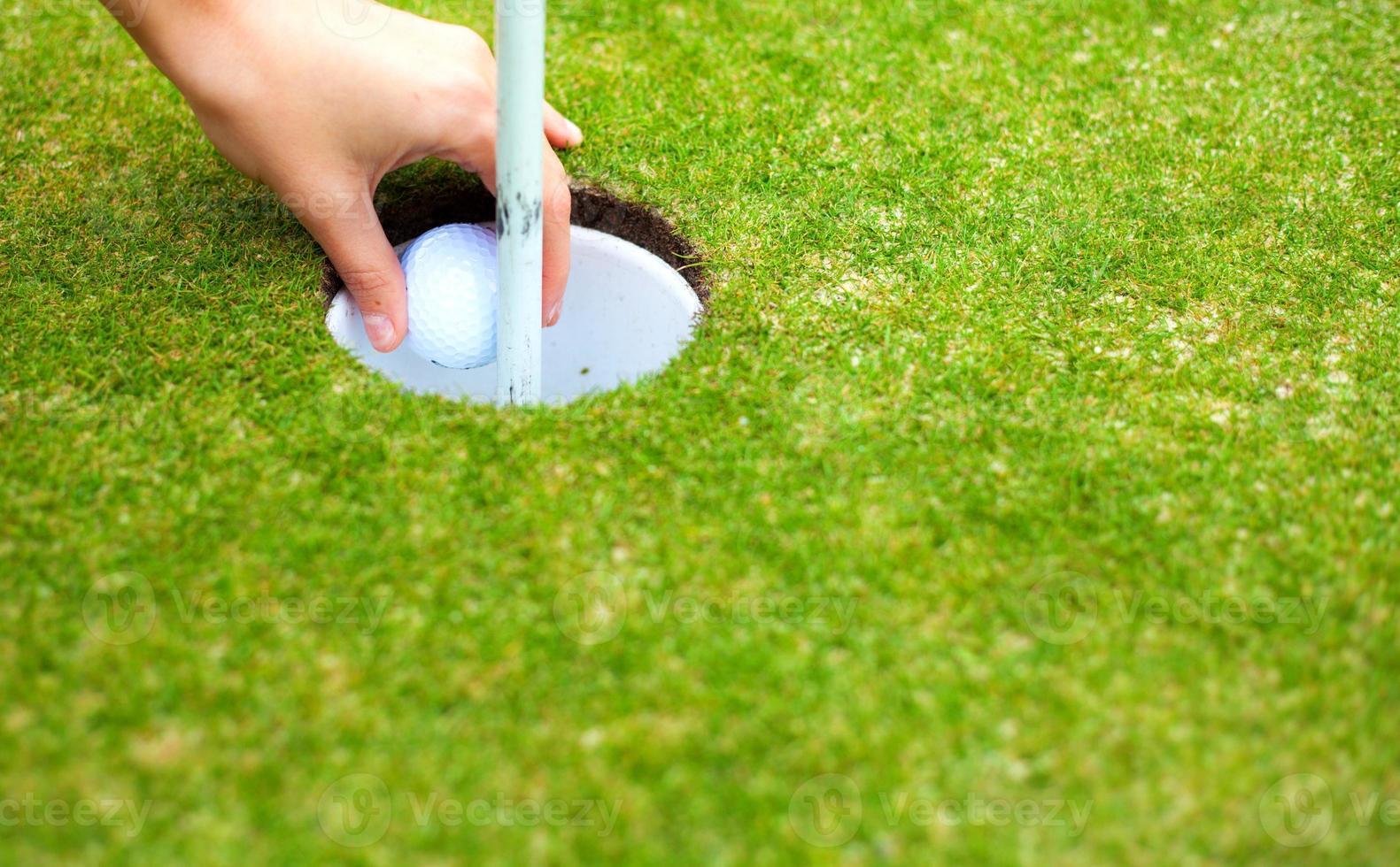 Spielerhand, die Golfball nach dem Schuss vom Becher entfernt foto
