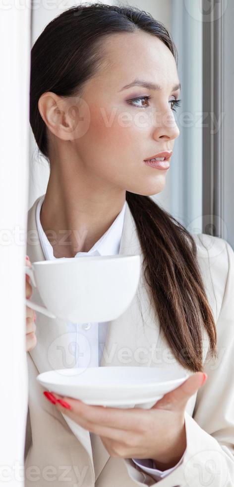 nachdenkliche Geschäftsfrau, die Kaffee im Büro trinkt foto