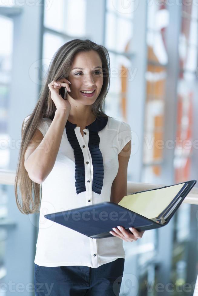 Geschäftsfrau auf Handy hält Ordner und lächelt foto