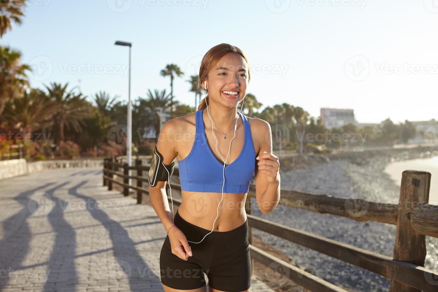 lächelnde Frau läuft an der Küste foto