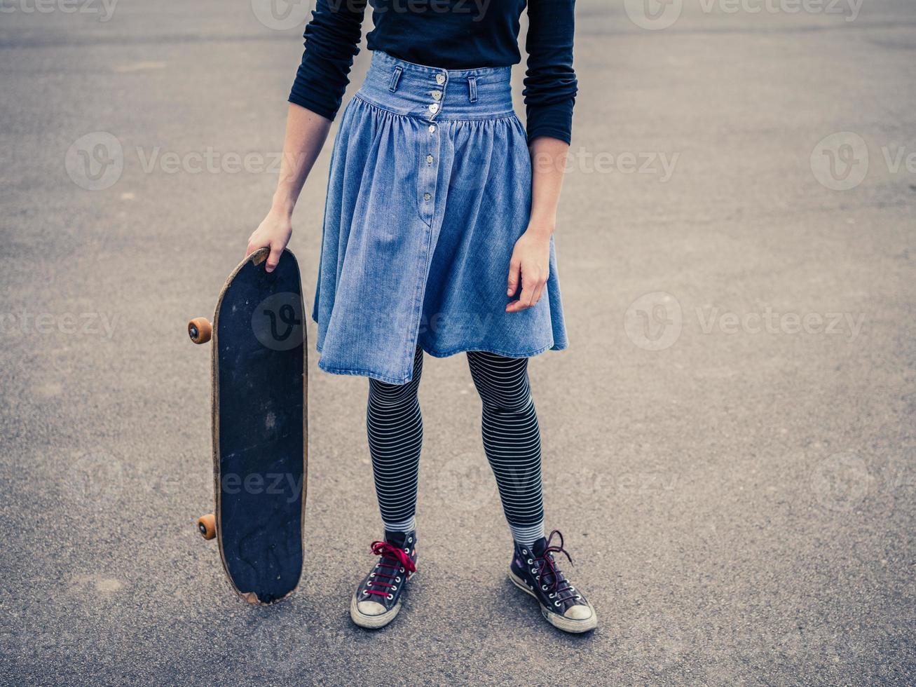 junge Frau, die im Park mit einem Skateboard steht foto
