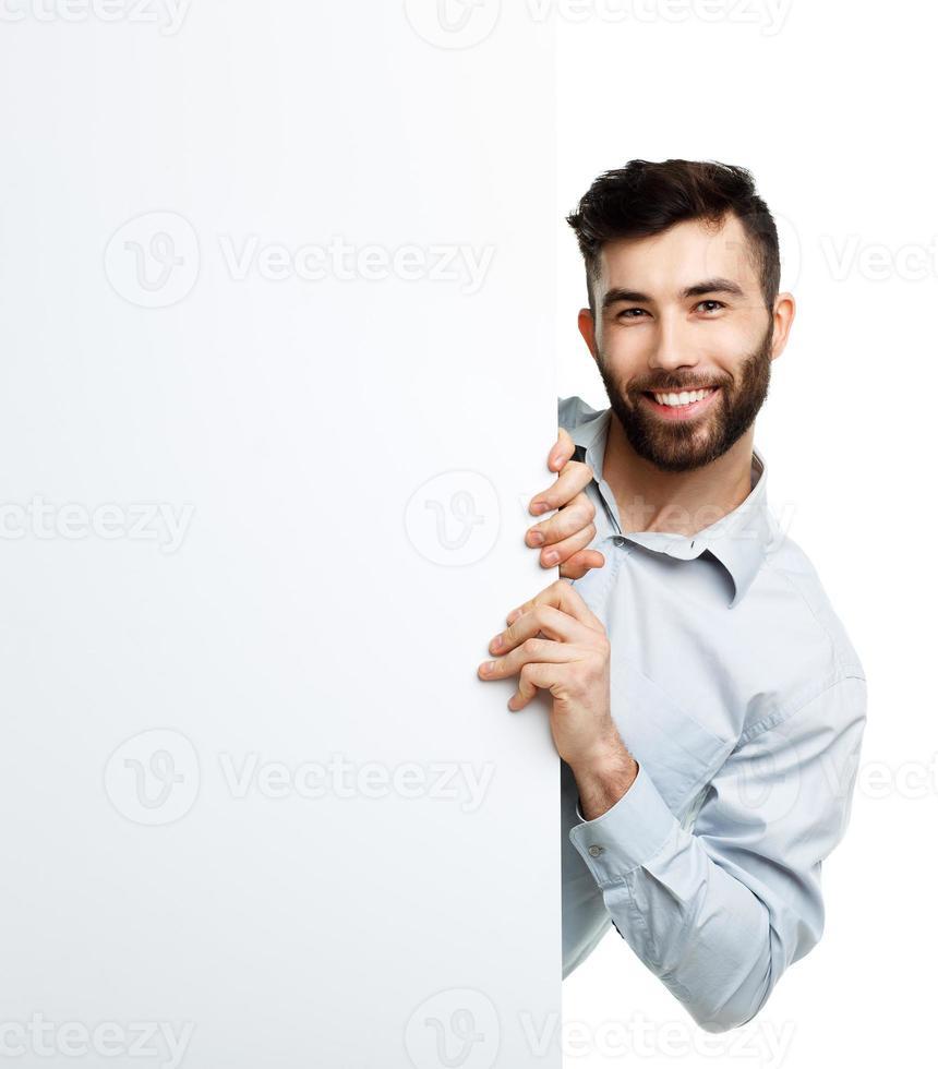 junger bärtiger Mann, der leeres Schild zeigt, lokalisiert über Weiß foto